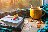 Autumn background. Cup of tea, cookies, books and plaid on windowsill with autumn forest outdoors. Still life with concept of spending autumn time at home Autumn still life.
