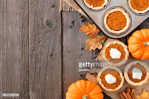 Autumn baking side border with pumpkin tarts over wood : Stock Photo