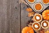 Autumn baking scene side border with pumpkin tarts over a wood background