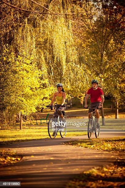 Autumn Bicyclists Cycling Exercising in Park Bicycle Path