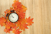 Black vintage clock with dried maple leaves on wooden . Autumn time change