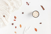 Autumn composition. Hot chocolate, blanket, autumn leaves, cinnamon sticks on white background. Flat lay, top view