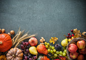 Autumn fruits and pumpkins with fallen leaves on rustic background. Top view