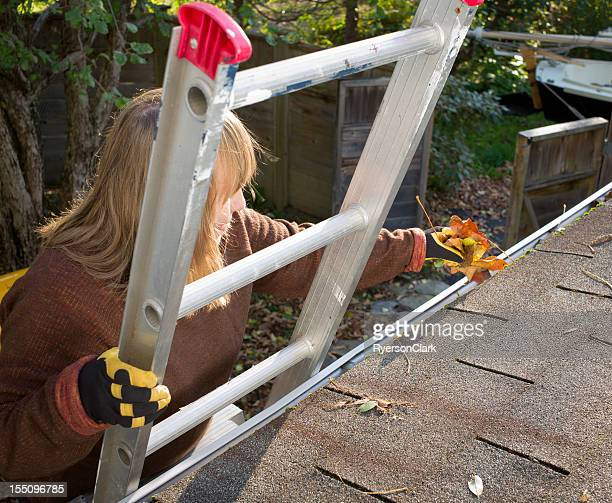 Autumn Gutter or Eavestrough Cleaning Senior Woman.