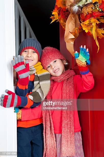 Autumn- Happy sibling waving at front door