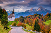 Image of the Bavarian Alps with Maria Gern Church and Watzmann mountain during beautiful autumn sunrise.