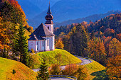 Image of the Bavarian Alps with Maria Gern Church during beautiful autumn sunset.