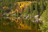 Colorful autumn foliage reflecting in a rocky lake.