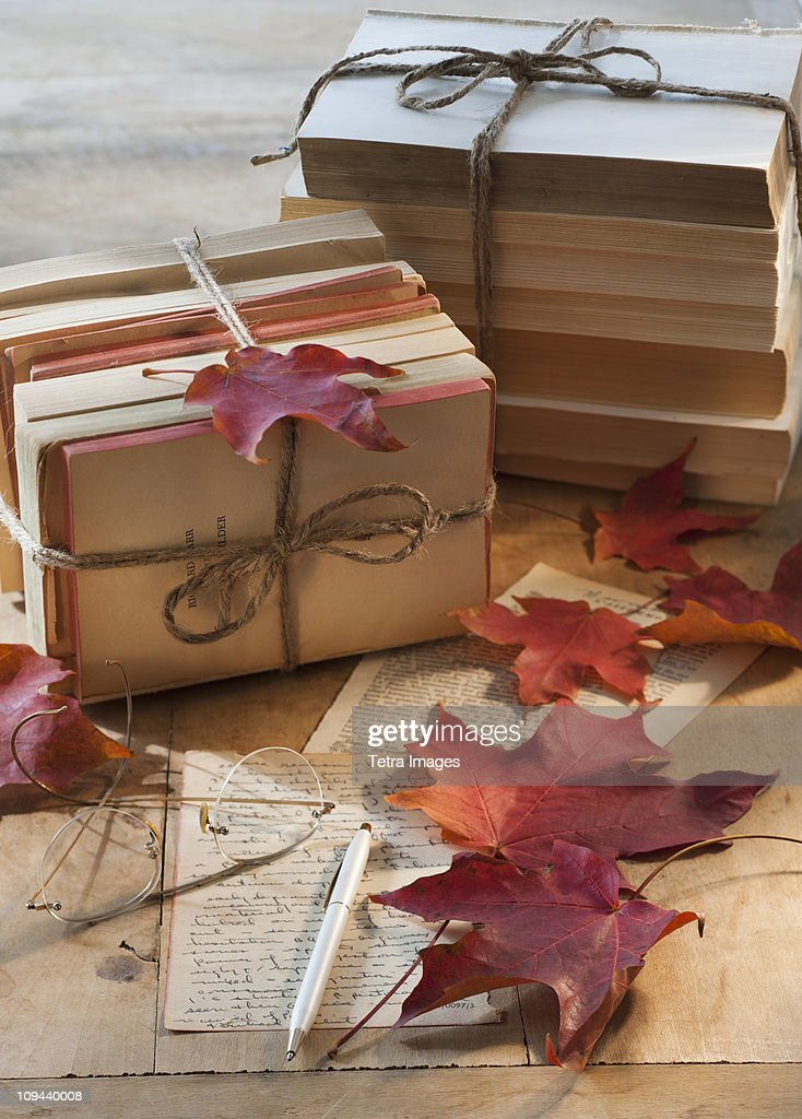 Autumn leaves on letter by books : Stock Photo