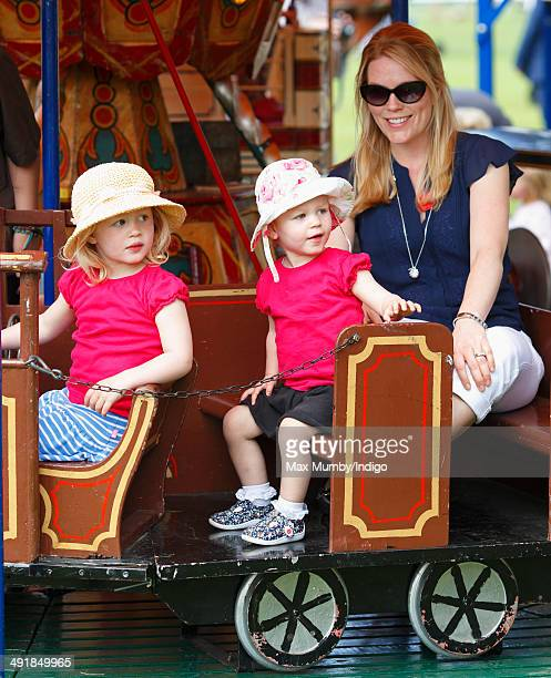 Autumn Phillips and daughters Savannah Phillips and Isla Phillips ride a merry go round during day 4 of the Royal Windsor Horse Show at Home Park on...