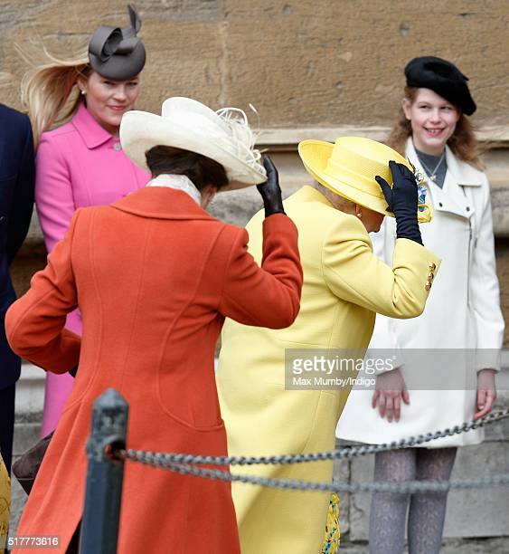 Autumn Phillips and Lady Louise Windsor look on as Princess Anne The Princess Royal and Queen Elizabeth II hold onto their hats in the strong wind as...