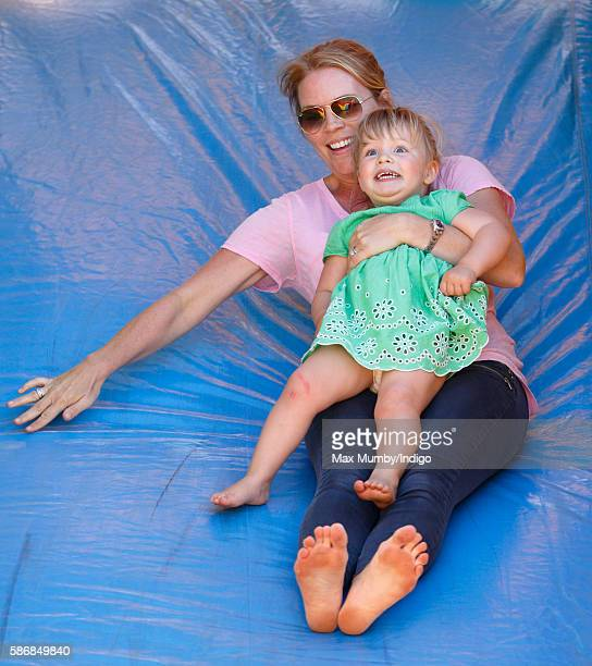 Autumn Phillips and Mia Tindall play on a bouncy castle slide as they attend day 2 of the Festival of British Eventing at Gatcombe Park on August 6...