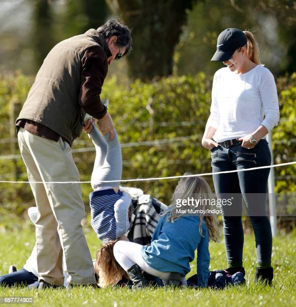 Autumn Phillips looks on as Vice Admiral Sir Timothy Laurence holds Mia Tindall upside down at the Gatcombe Horse Trials at Gatcombe Park on March 25...