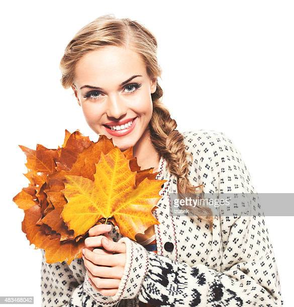 Autumn portrait of cheerful blond hair young woman holding leaves