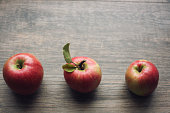 Autumn season still life with three apples over rustic wooden background. Copy space, horizontal.