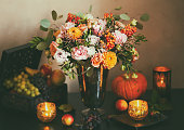 Autumn still life with flowers, pumpkin, fruits and candles. Toned,vintage style