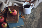 Autumn still life with apples, warm blanket, books, coffee cup and leaves over rustic wood background. Horizontal.