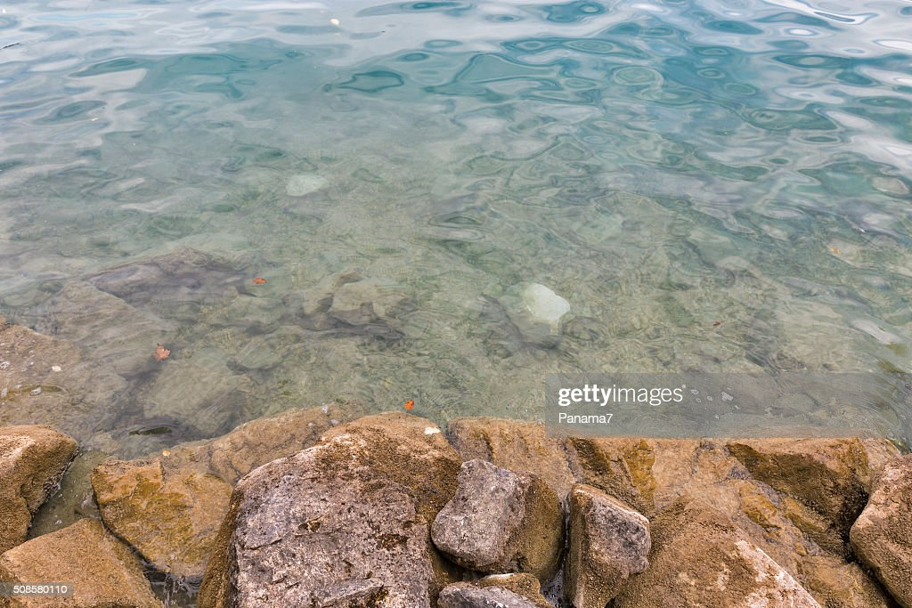 autumn stone lake shore with transparent water closeup : Stock Photo
