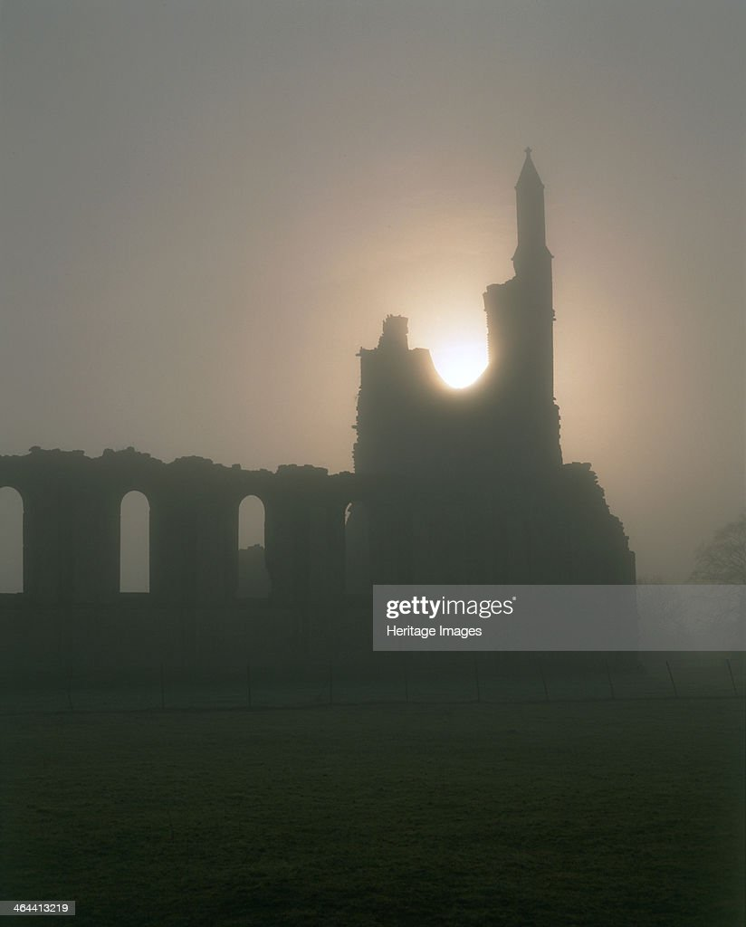 Autumn sunset at Byland Abbey, North Yorkshire, 1998. Photographed late on a foggy autumn afternoon, the sun sets through the west window of the ruined abbey church. The Cistercian abbey of Byland sits in the shadow of the Hambledon Hills.