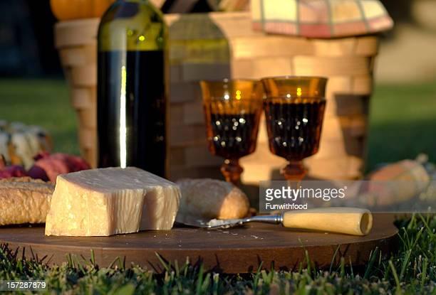 秋の夕日のチーズ&ワインボトル 1 本、屋外でのお食事用のピクニックバスケット