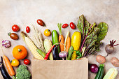 Autumn vegetables in shopping paper grocery bag on kitchen table top view. Supermarket concept.