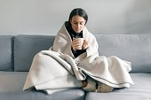 Autumn winter portrait of young girl resting at home on the sofa with cup of hot drink, under warm blanket.