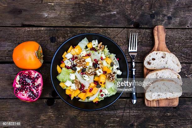 Autumnal salad with kaki, feta cheese, iceberg lettuce, pumpkin seeds, pomegranate and walnuts