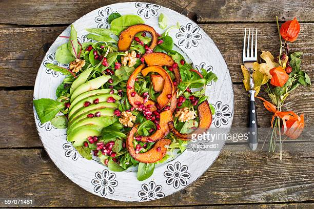 Autumnal salad with squash, pomegranate seeds, avocado and walnuts
