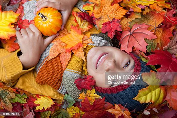 Autumn-Smiling boy holding small pumpkin