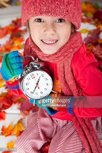 Autumn-Smiling girl holding alarm clock