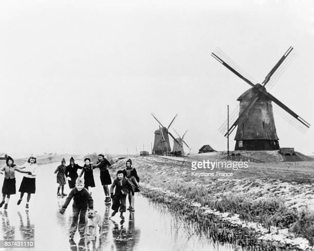 Aux pieds des moulins des jeunes Hollandais font avec bonheur du patinage sur un canal gelé pratique interdite sous l'occupation en Hollande en 1946