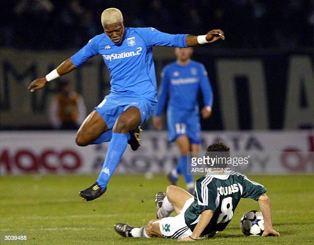Auxerre's Djiblil Cisse is tackled by Panathinaikos' Yannis Goumas during their third round UEFA cup football match in Athens 03 March 2004 AFP...
