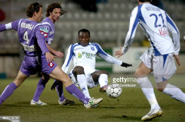 Auxerre's Kenian forward Dennis Oliech fights for the ball with Toulouse's French defender Dominique Arribage and Toulouse's middfielder Pantxi...