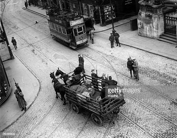 Auxiliaries wearing Tam o' Shanter bonnets talk to a postman with a GPO mail cart in Dublin The Auxiliaries are further reinforcements for the Royal...