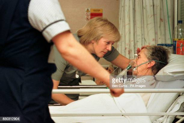 Auxiliary Nurse Rosaleen McCormack tends to an elderly patient at Glasgow's Royal Infirmary Hospital as the country struggles with the number of...