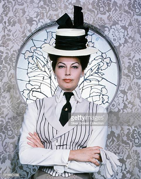 Ava Gardner US actress in period costime with a blackandwhite striped waistcoat and a white hat with a black band with her arms folded standing in...