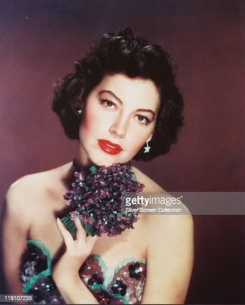Ava Gardner US actress wearing a purpleandgreen shoulderless dress and holding a purpleandgreen corsage in a studio portrait circa 1955