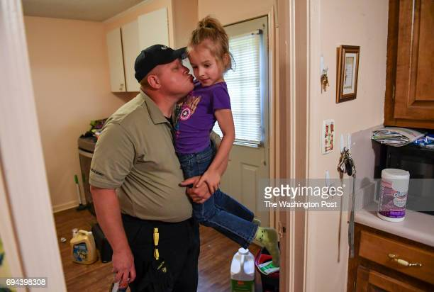 Ava Olsen who was on the playground during the Townville Elementary shooting gets a hug and kiss from her dad David after he arrived home from work...