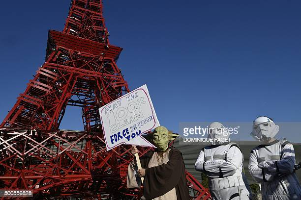 TOPSHOT Avaaz activists dressed as Star Wars' Yoda and stormtroopers stand in front of a replica of the Eiffel Tower as they protest during the COP21...