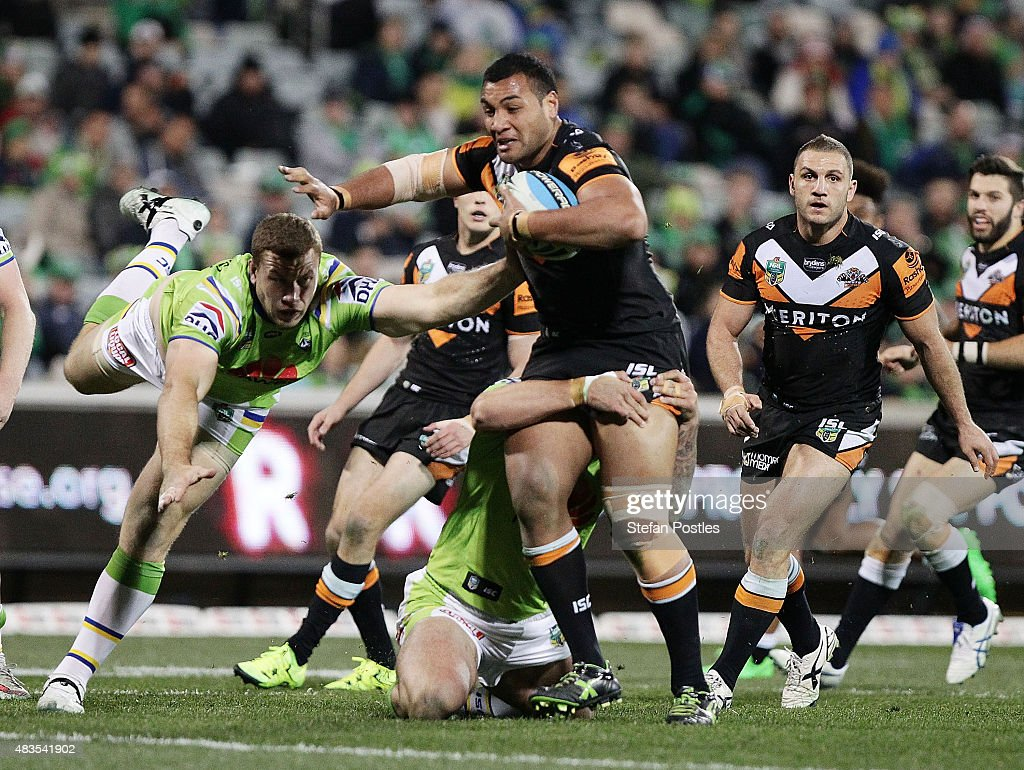 Avagalu Seumanufagai of the Tigers is tackled during the round 22 NRL match between the Canberra Raiders and the Wests Tigers at GIO Stadium on August 10, 2015 in Canberra, Australia.