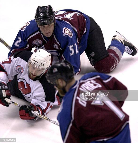 Avalanche Adam Foote takes down Devils Petr Sykora as Avs Greg de Vries takes the puck by in the first period of game three of the Stanley Cup finals...