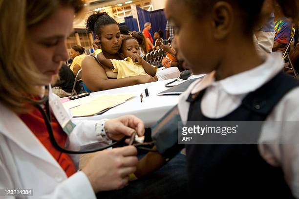 Avanna Parent of New Orleans LA holds her two yearold son Leo as Dr Kim Davis of Raleigh NC takes a blood pressure test on her five yearold daughter...