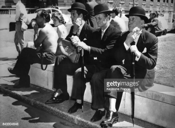 Avec la canicule ces trois hommes portant costume cravate et chapeau melon s'épongent le visage transpirant à Londres RoyaumeUni