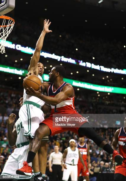 Avery Bradley of the Boston Celtics defends a shot by John Wall of the Washington Wizards during the second quarter at TD Garden on March 20 2017 in...