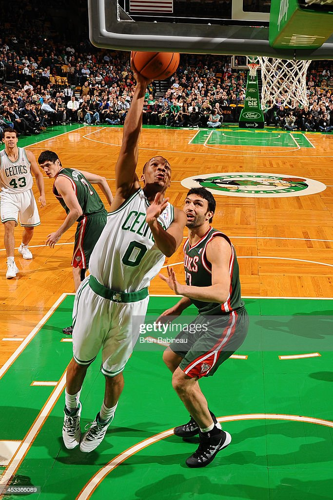 Avery Bradley of the Boston Celtics shoots against Zaza Pachulia of the Milwaukee Bucks on December 3 2013 at the TD Garden in Boston Massachusetts...