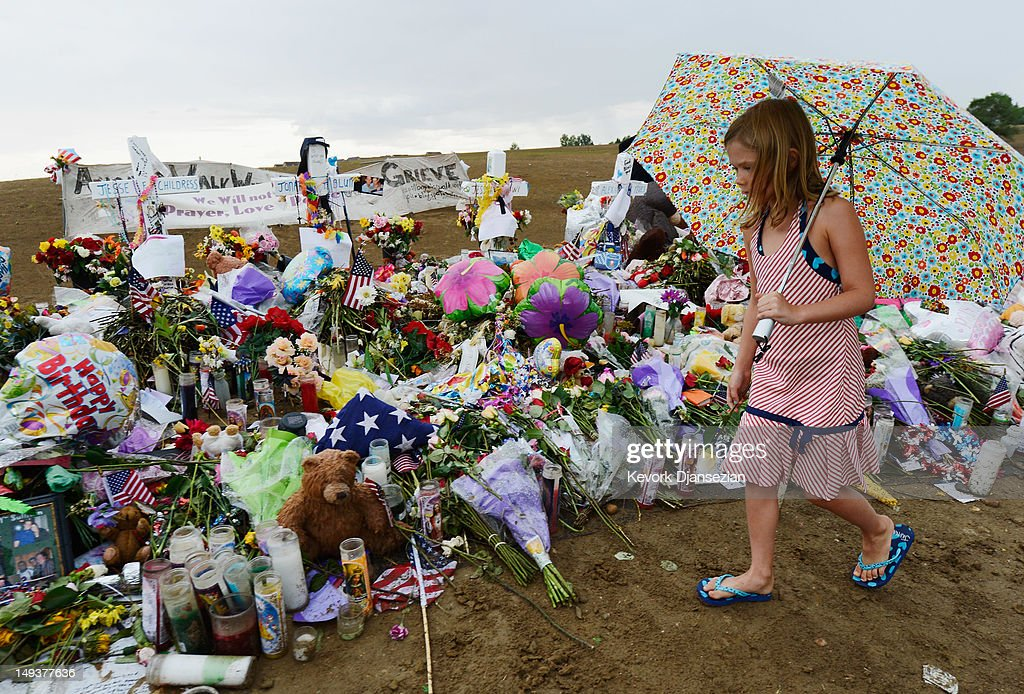 Avery Gillespie, 7, places flowers at a memorial setup across the street from the Century 16 movie theatre on July 27, 2012 in Aurora, Colorado. Twenty-four-year-old James Holmes is suspected of killing 12 and injuring 58 others July 20 during a shooting rampage at a screening of 'The Dark Knight Rises' in Aurora, Colorado.