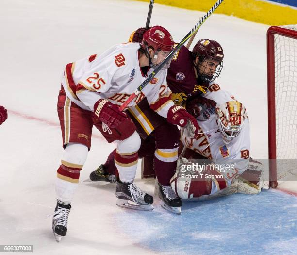 Avery Peterson of the Minnesota Duluth Bulldogs is pinched between Tanner Jaillet of the Denver Pioneers and his teammate Blake Hillman during the...