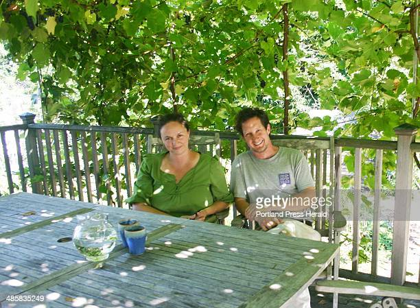 Lisa Fernandes and her husband David Whitten sit on their deck in the dappled sunshine created by the grape arbor loaded with Bluebell and Beta...