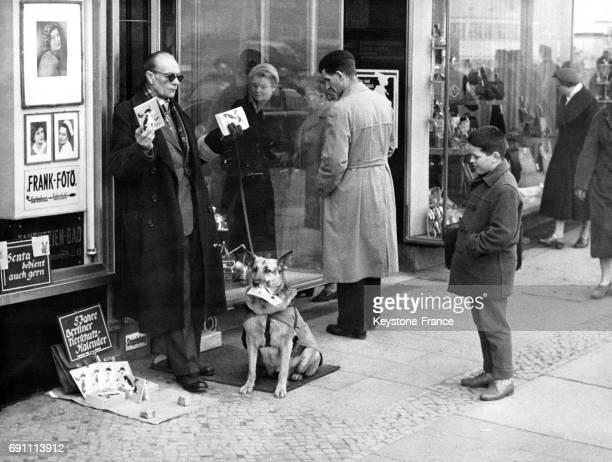 Aveugle et son chien vendant des calendriers à Berlin Allemagne le 28 novembre 1958