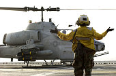 Aviation Boatswain's Mate 3rd Class Tara Fernando from Laguna NM launches an AH1W 'Super Cobra' helicopter from the 'Scarfaces' of Helicopter Attack...